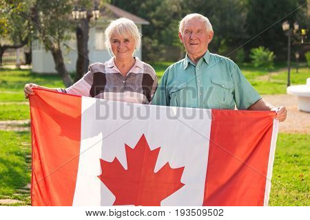 Senior couple holding Canadian flag. Man and woman outdoors. Life in Canada.