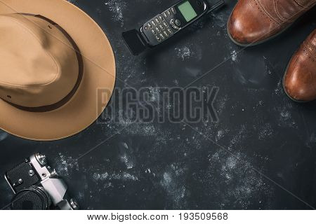 Tourism and travel concept. Vintage film camera, brown shoes, fedora hat and old mobile phone on black stone background. Free space for your text.