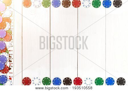 Playing cards and poker chips on white wooden background. Top view. Copyspace. Poker. Summer. Sun flare