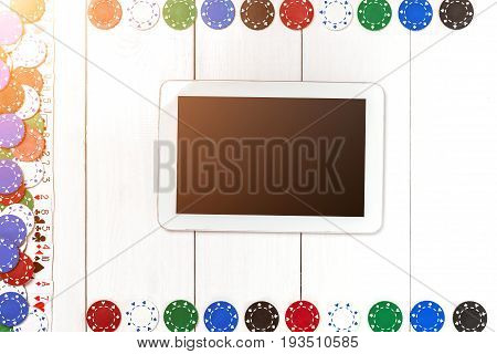 Playing cards, poker chips and tablet on white wooden background. Top view. Copyspace. Poker. Summer. Sun flare