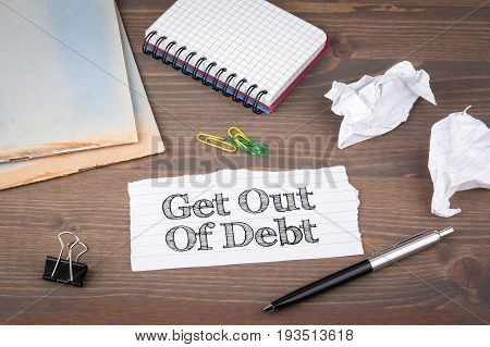 Get Out of Debt. paper sheet from the booklet on the wooden table.
