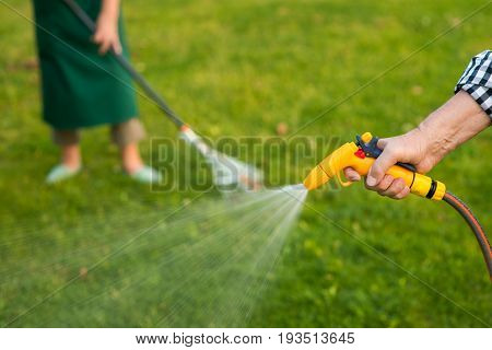 Old hand holding water hose. Tool spraying water. Buy quality gardening equipment.