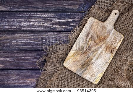 Chopping board on dark wood background, cutting tray over burlap tablecloth, top view