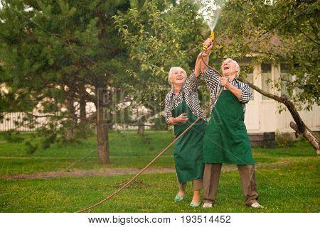 Senior people having fun. Man and woman, water hose. Under the rain.