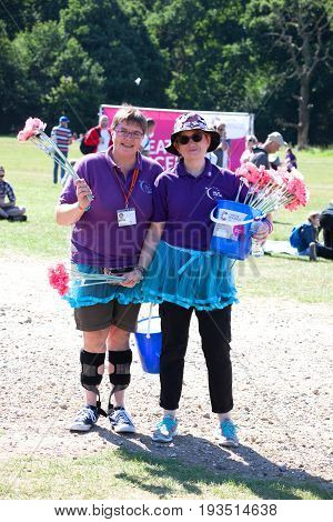 SOUTHAMPTON UK - July 2 2017: Race for Life women run and walk to raise money for Cancer Research charity in Southampton UK. Ladies promoting Cancer Research with artificial flowers.