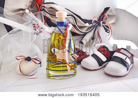 greek Orthodox christening objects - baby shoes, baptism oil, soap and candles