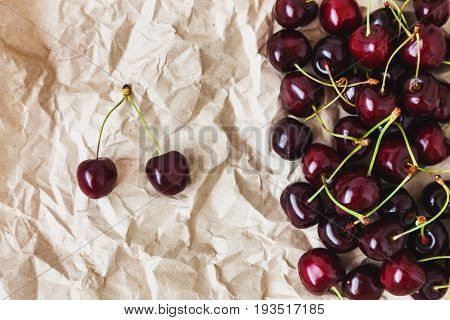 Fresh Cherry Berries Lie On Rumpled Parchment Paper. Concept Of Healthy And Healthy Nutrition