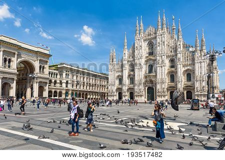 MILAN, ITALY - MAY 16, 2017: Tourists take pictures in front of the Milan Cathedral (Duomo di Milano) on a summer day. Milan Duomo is the largest church in Italy.