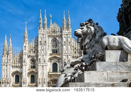 Sculpture of a lion as part of the monument to Victor Emanuel II in the Piazza del Duomo in Milan, Italy. The Milan Cathedral (Duomo di Milano) in the background.