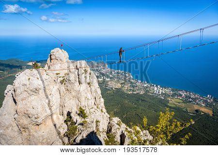 CRIMEA, RUSSIA - MAY 19, 2016: Tourist walking on a rope bridge on the Mount Ai-Petri. Ai-Petri is one of the highest mountains in Crimea and tourist attraction.