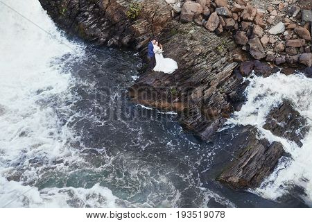 Beautiful couple in love kissing while sitting on rocks near sea. Wedding couple at sunset and sea love and tender feelings. Loving couple resting. Wedding ceremony outdoors. Perfect couple blurred