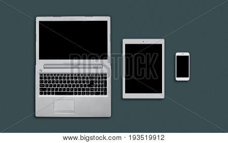 Mock Up Of Office Desk With Laptop, Tablet And Smartphone. Top View Of Modern Gadgets Laying On Flat