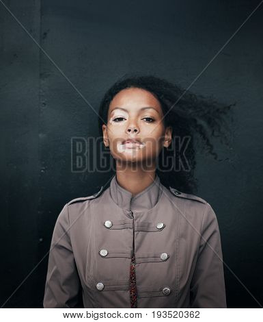 beautiful young brunette woman with vitiligo disease on the black background