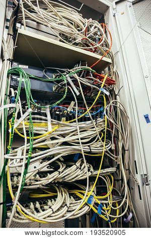 Inside cabinet with switchboard and other telecommunication mobile network hardware equipment with many cables, vertical image