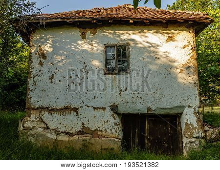 Old traditional Serbian rural house and green trees
