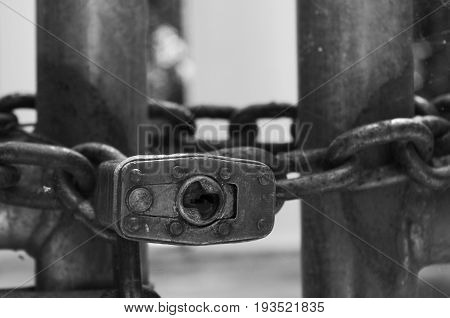 Close up of a key hole of a pad lock black and white.