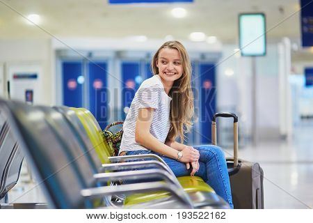 Tourist Girl With Backpack And Carry On Luggage In International Airport, Waiting For Flight