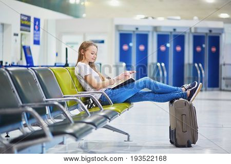 Young Travelerin International Airport Reading A Book While Waiting For Her Flight