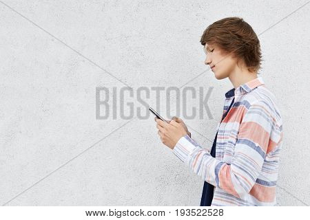 Stylish Teenage Boy Standing Sideways Holding Cell Phone Isolated Over White Concrete Wall With Copy