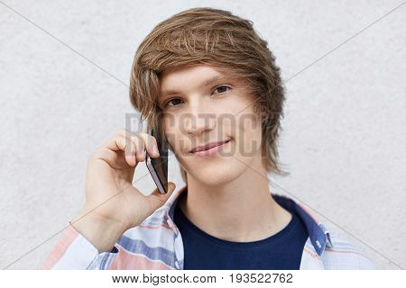 Headshot Of Handsome Stylish Hipster Boy Calling His Friend Using Smartphone Looking Directly Into C