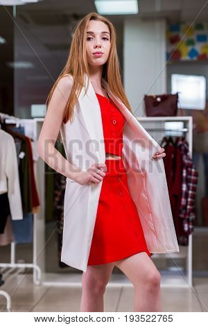 Portrait of a young female model looking in mirror wearing red top and skirt co-ord set and long vest standing in a show room.