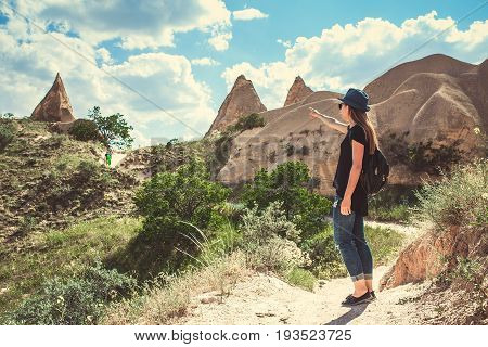 The tourist girl shows the way in the hilly region of Cappadocia in Turkey. Hiking, travel, walk.