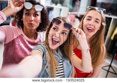 Three female friends taking selfie making faces raising sunglasses in clothing and accessories outlet.