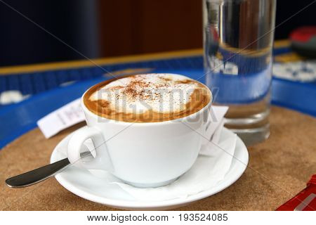 Cup of coffee with froth the powdered cinnamon on a little table in cafe