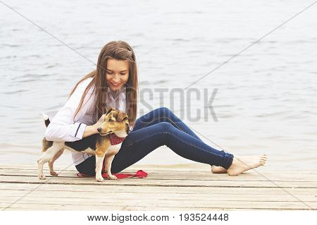 Playing With Dog. Horizontal Shot Of Beautiful Young Woman In Casual Clothing Looking At Dog And Smi
