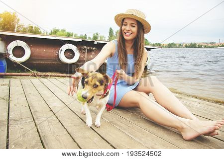 Hey, Come To Me, Dear. Horizontal Shot Of Tender Beautiful And Young Woman In Hat Is Calling Dog To