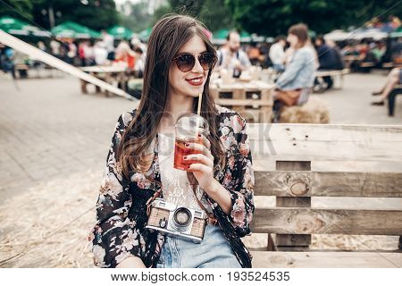 Stylish Hipster Woman In Sunglasses With Lemonade. Boho Girl In Denim And Bohemian Clothes, Holding