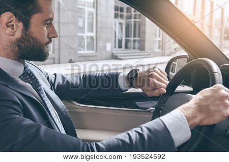 Young business person test drive new vehicle checking time