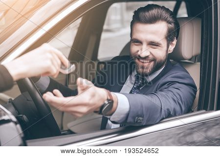 Young business person test drive new vehicle getting keys