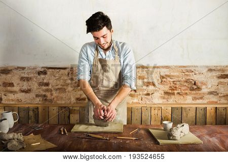 potter, workshop, ceramics art concept - standing young brunette man dressed in an apron, male hands knead the fireclay, a ceramist with raw materials on wooden table with sculpting tools set