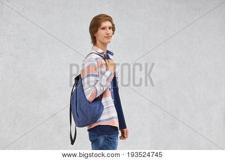 Teenage Boy Standing Sideways Holding Rucksack Wearing Shirt And Jeans Posing Against White Concrete