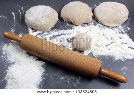 Dough, flour and rolling pin close up image