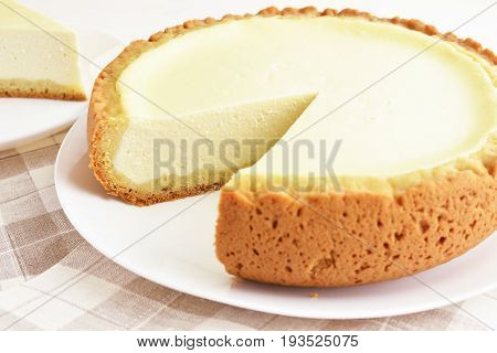 homemade finnish cottage cheese pie dessert on white porcelain plate, linen and wooden background