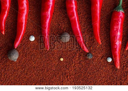 red hot chili peppers, popular spices concept - closeup on decorative pattern of red chili pods on a brown background from a powder of indian curry, flat lay, free space for text