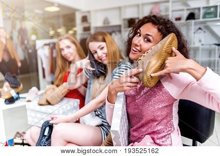 Smiling young women sitting in a womenswear store playing with new footwear using shoes like a phone.