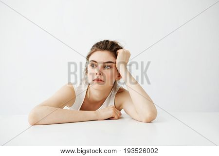 Bored tired young pretty girl with bun thinking dreaming sitting at table over white background. Copy space.