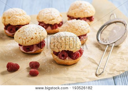 Eclairs with mascarpone cream and raspberries .