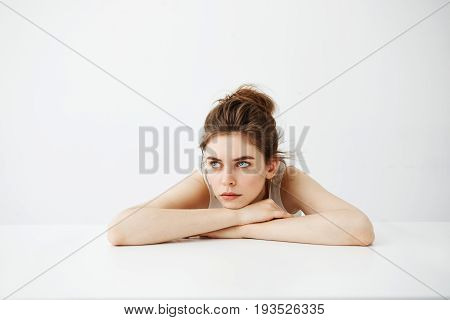 Bored tired young pretty girl with bun thinking dreaming lying on table over white background. Copy space.