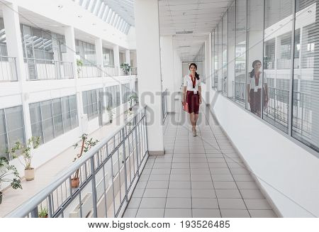 Business Woman Walking Along the Office Corridor. Smiling Businesswoman Goes Against White Offices Background. A young pretty girl in a white blouse and red skirt is walking along the corridor.