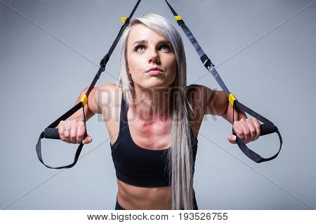Sexy Female Fitness Model Training On A Home Training Device In A Studio