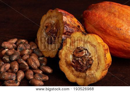 Close-up of cacao seeds with cut cocoa fruit on dark wooden background