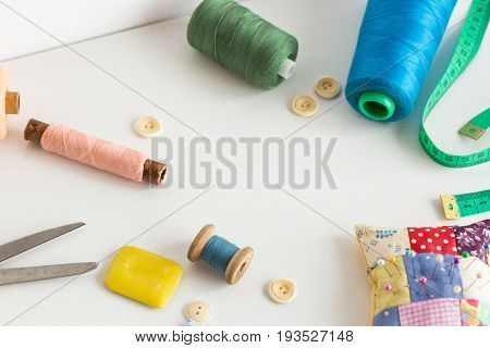 sewing tools, patchwork, tailoring and fashion concept - closeup on white desk in studio, colorful thread spools, measuring meter, buttons, many worked scissors, pincushion, equipment for needlework.