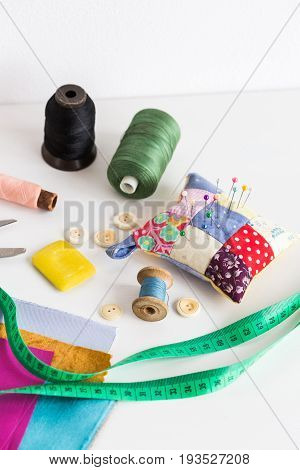sewing tools closeup, patchwork, tailoring and fashion concept - measuring tape, thread spools, pincushion, buttons, scissors, pieces of colored patchwork fabric, soap on white desk, vertical