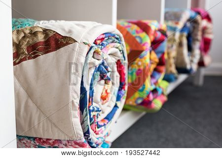 patchwork, sewing and fashion concept - bright finished quilts in the studio at white shelves with three storage compartments, the warehouse of finished products, side view, selective focus