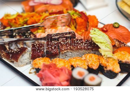 Assortment of different sushi rolls served on a plate, decorated catering table