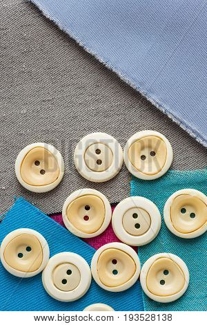 sewing tools, patchwork, tailoring and fashion concept - close-up on scattering of white clothing buttons over pieces of blue, gray patches of fabric, flat lay, top view, vertical